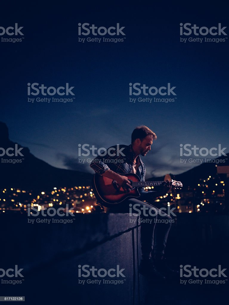 Hipster Teenager Boy Playing Guitar On Rooftop On Summer Evening