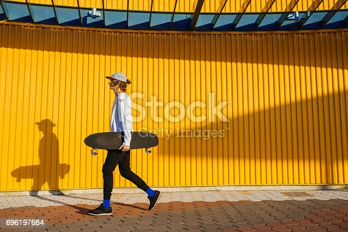 Young skater boy walking outdoors with longboard