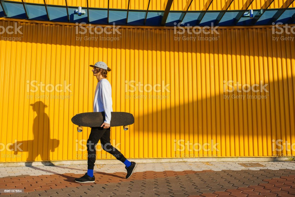 Hipster teenager walking with longboard stock photo