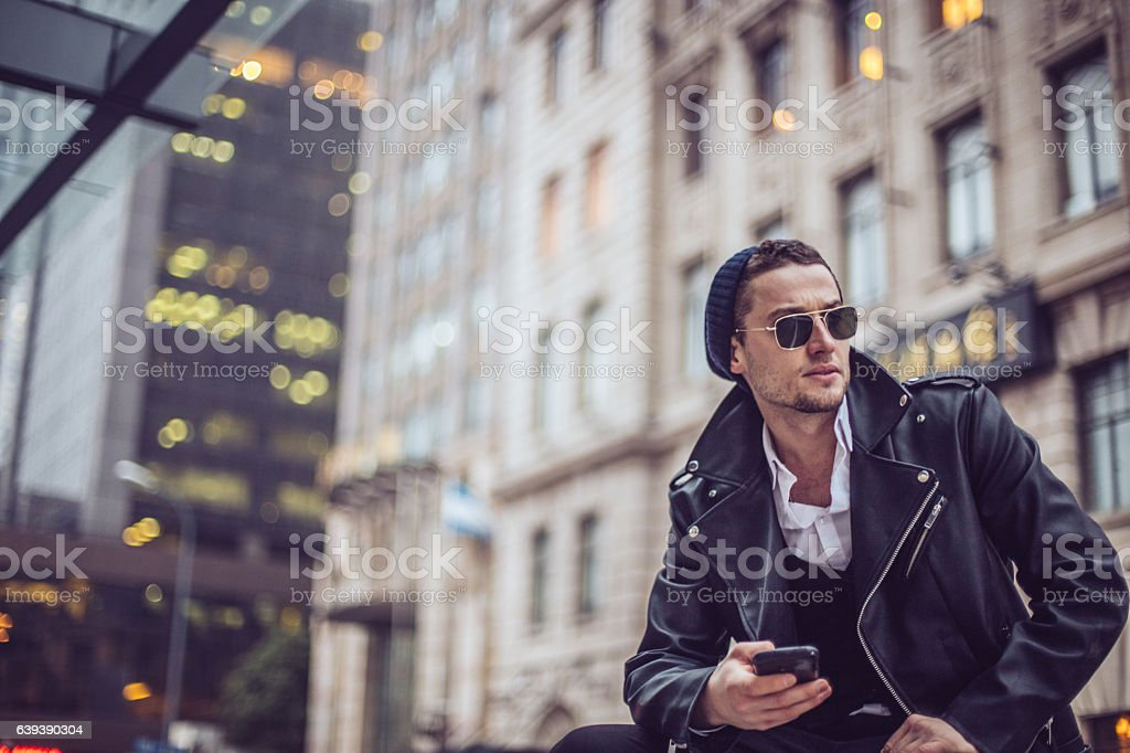 Hipster texting on a mobile phone stock photo