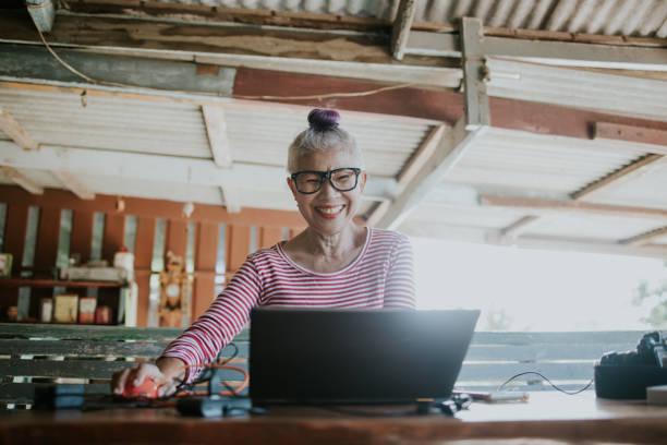 彼女の家で彼女の仕事をするためにコンピュータを使用してヒップスタータイのシニアフォトグラファー - showus ストックフォトと画像