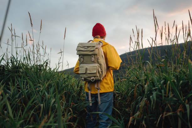 Hipster-Reisende tragen Rucksack und gelben Regenmantel mit Blick auf den Berg. Alleinmann auf reisen in skandinavischen authentischen Landschaft – Foto