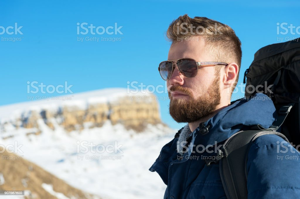 A hipster traveler with a beard wearing sunglasses in nature stock photo
