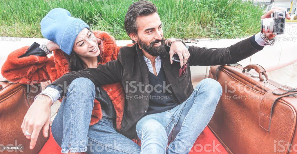 Hipster trendy couple taking selfie with old vintage camera sitting on bench - Cheerful young people having together waiting for taxi - Fashion and trend concept - Main focus on him - Warm filter - foto stock
