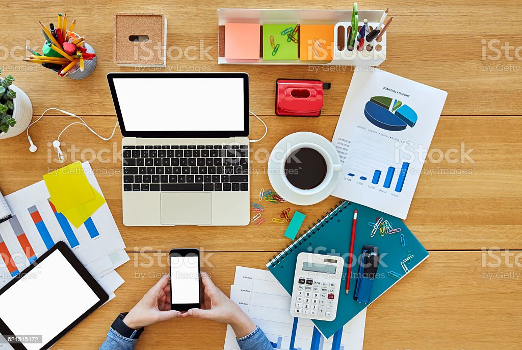 Gentil Hipster Using Smart Phone Surrounded By Office Supplies At Desk  Royalty Free Stock Photo
