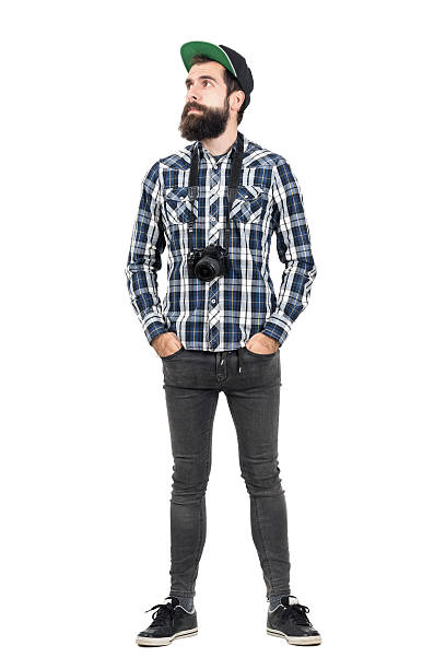 Hipster wearing black dslr camera over neck looking away Relaxed hipster wearing black dslr camera over neck with hands in pockets. Full body length portrait isolated over white studio background men in tight jeans stock pictures, royalty-free photos & images
