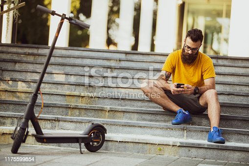 Hipster with an electric scooter talking on the phone
