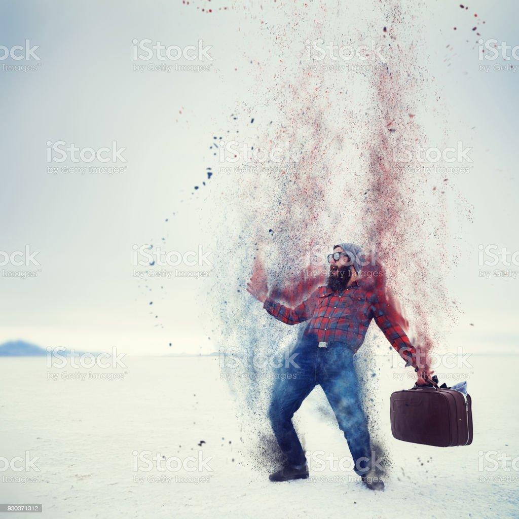 hipster with beard and suitcase turning into dust on the salt flats stock photo