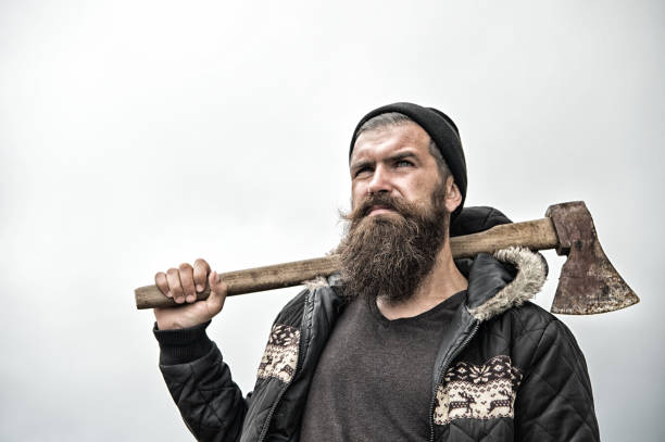 Hipster with beard on serious face carries axe on shoulder sky on background, copy space. Lumberjack brutal and bearded holds axe. Brutal lumberjack concept. Man in hat and warm jacket looks brutally Hipster with beard on serious face carries axe on shoulder sky on background, copy space. Lumberjack brutal and bearded holds axe. Brutal lumberjack concept. Man in hat and warm jacket looks brutally. lumberjack stock pictures, royalty-free photos & images