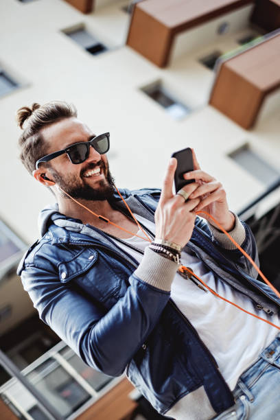 Hipster with headphones smiling and reading message Hipster with headphones smiling and reading message on the phone man bun stock pictures, royalty-free photos & images
