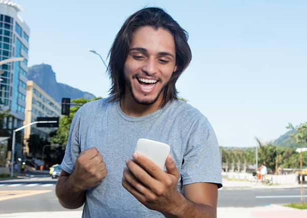 hipster with long brunette hair receiving good news on phone - die besten apps stock-fotos und bilder