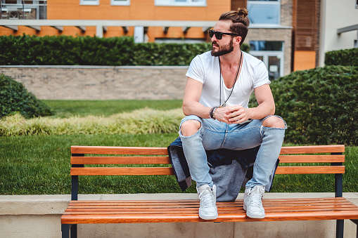 Hipster with man bun sitting on the park bench on a sunny day
