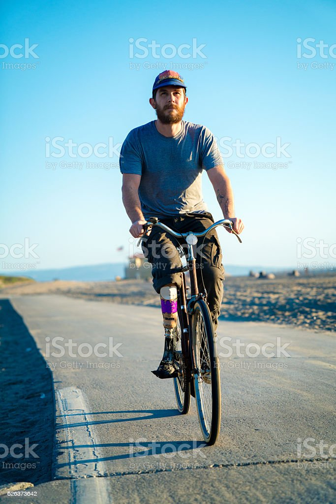 Hipster with prosthetic leg riding a bike at the beach stock photo