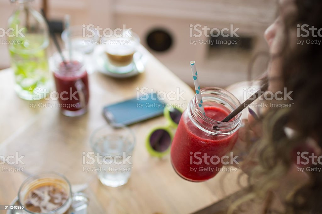 Hipster woman drinking raspberry smoothie stock photo