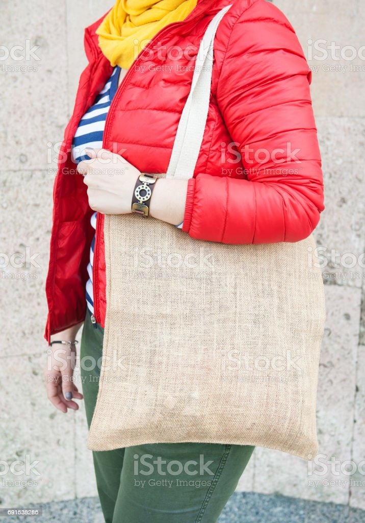 Hipster woman holding empty canvas bag outdoor. Template mock up stock photo