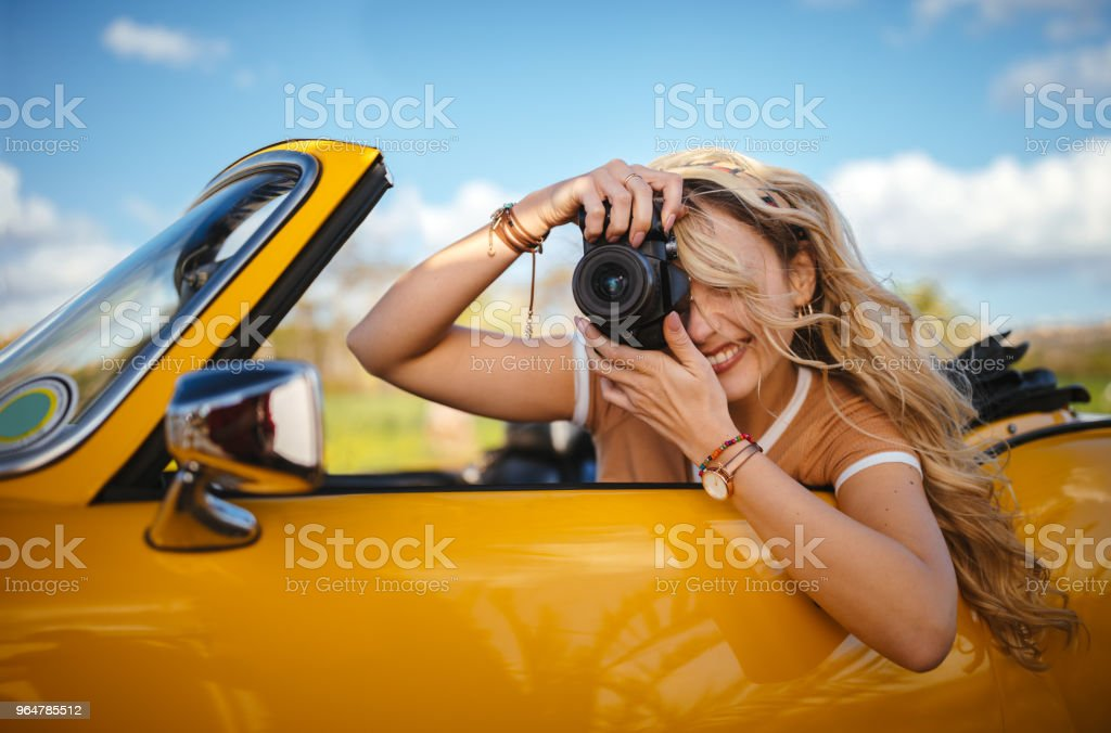Hipster woman in retro convertible car taking photos with camera royalty-free stock photo