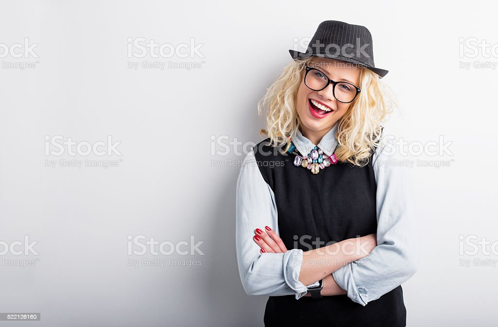 Hipster woman leaning against the wall with crossed hands stock photo