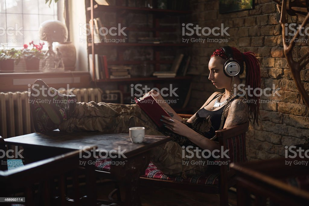 Hipster woman reading a book while listening music on headphones. stock photo