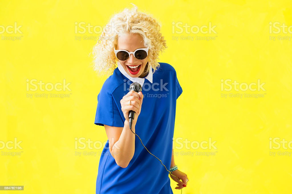 Hipster woman singing in microphone stock photo