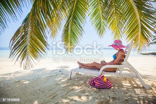 istock Hipster woman sitting and chilling on easy chair on beach, Maldives 811846856