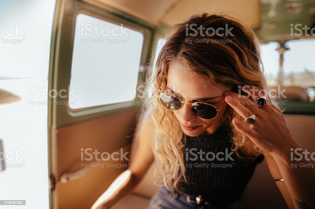 Hipster Woman sitting in van with open door to beach stock photo