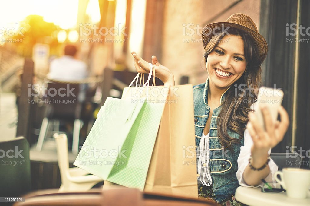 Hipster woman taking selfies with shopping bags in a coffee-shop stock photo