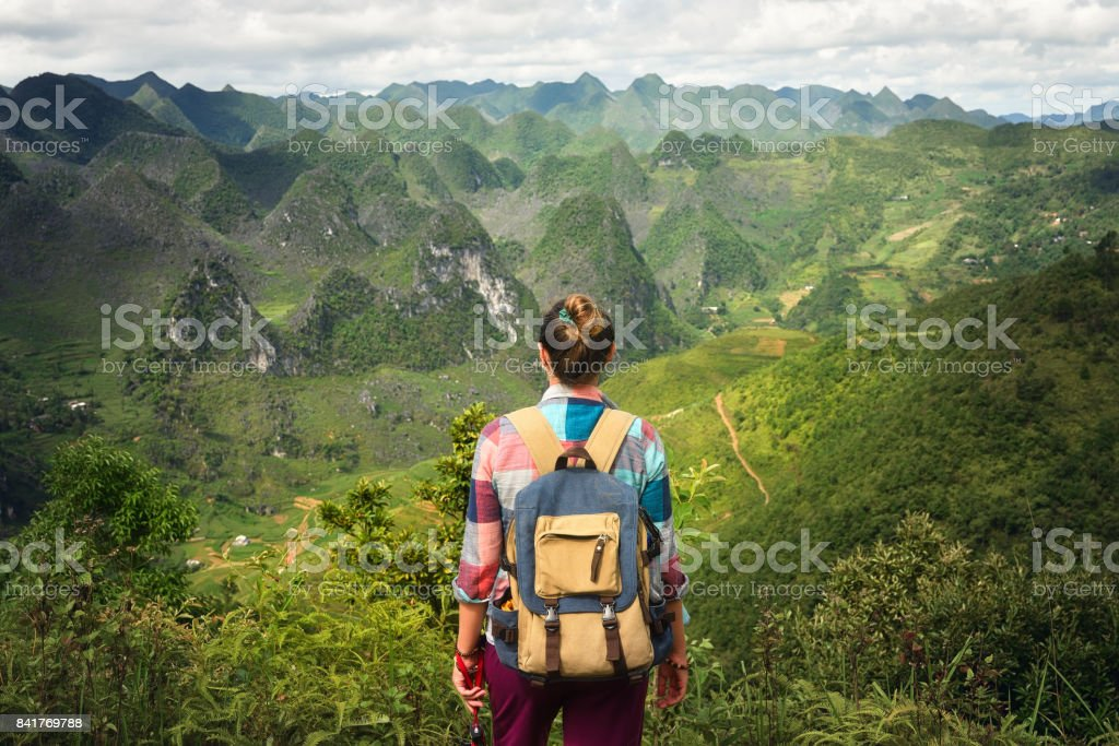Hipster woman traveler with backpack enjoying a beautiful view of the unusual forms of mountains stock photo