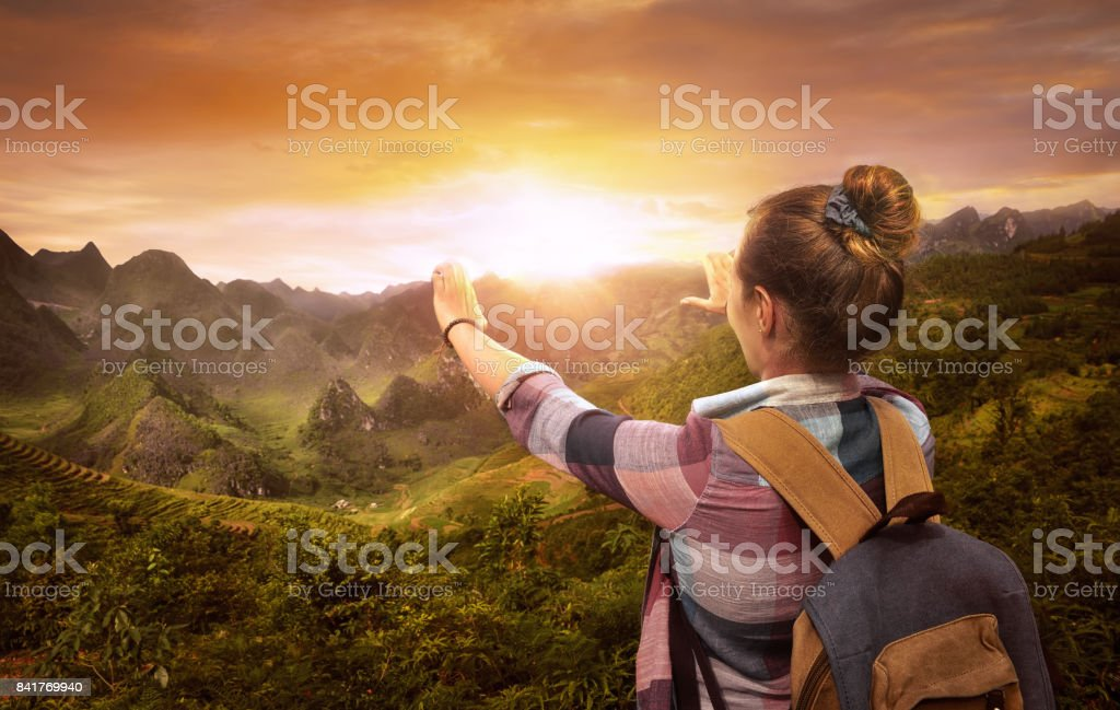 Hipster woman traveler with backpack enjoying beautiful sunset over mountains stock photo