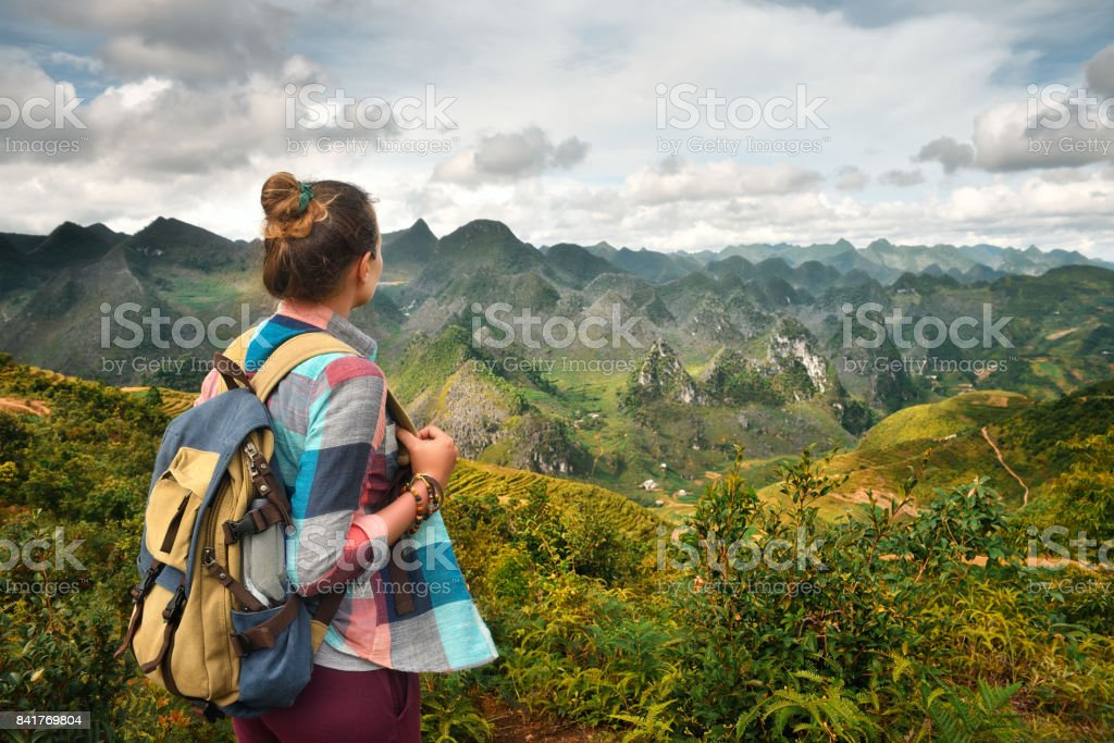 Hipster woman traveler with backpack enjoying beautiful view of mountains stock photo