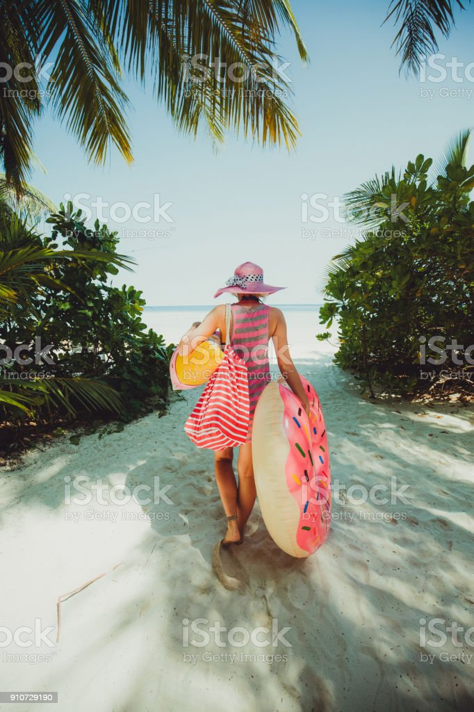 Hipster woman walking through jungle on the road to coast, Maldives stock photo