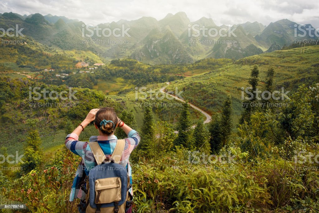 Hipster woman with backpack takes pictures  beautiful view of mountains stock photo