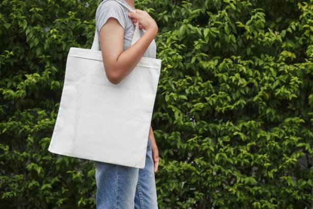 Hipster Frau mit weißer Baumwolltasche auf grünem Blatt Hintergrund – Foto