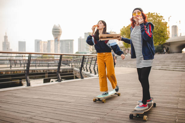 Hipster women eating pizza and riding long boards stock photo