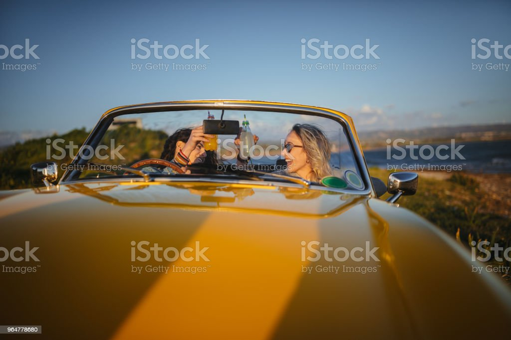 Hipster women with vintage convertible car drinking soda at beach royalty-free stock photo