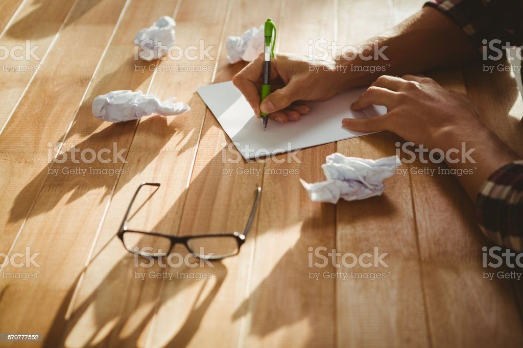 Hipster schreiben auf Papier am Schreibtisch im Büro – Foto