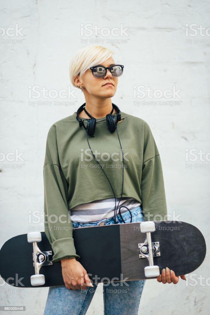 Hipster junge blonde Frau mit skateboard Lizenzfreies stock-foto
