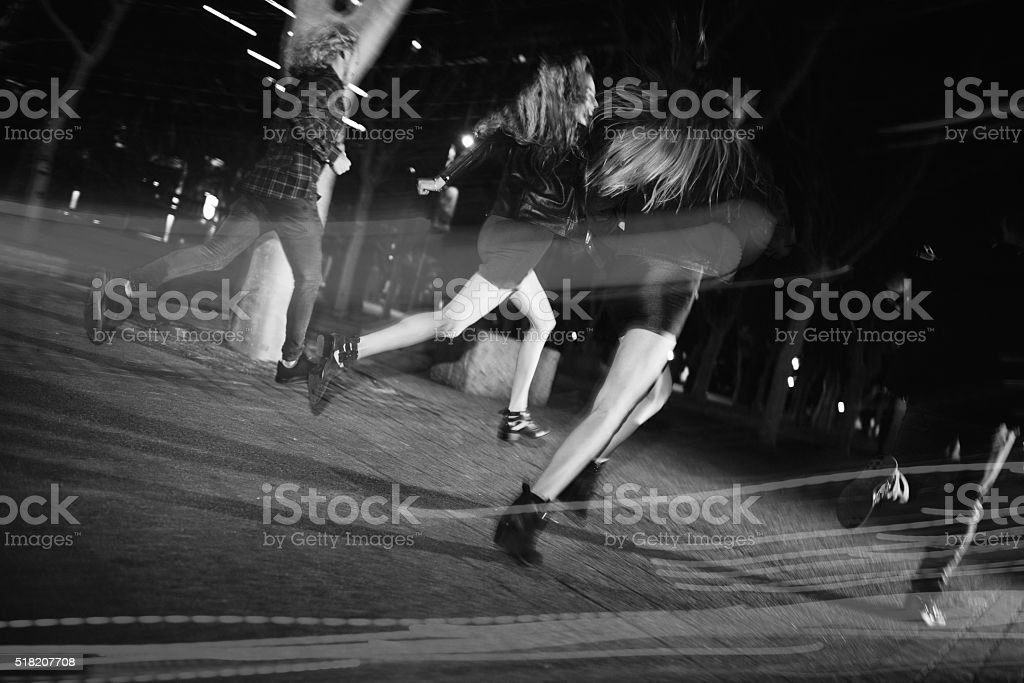 Hipster young friends running happy in town at night stock photo