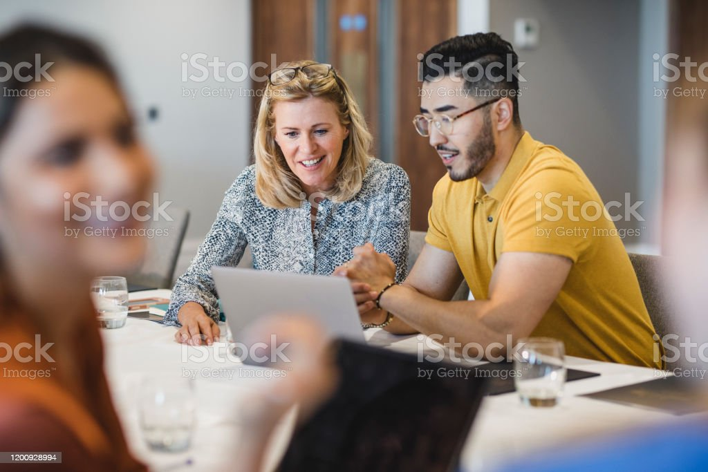 Hipster young man showing female colleague laptop Mature businesswoman smiling with employee, working together, collaboration, teamwork 25-29 Years Stock Photo