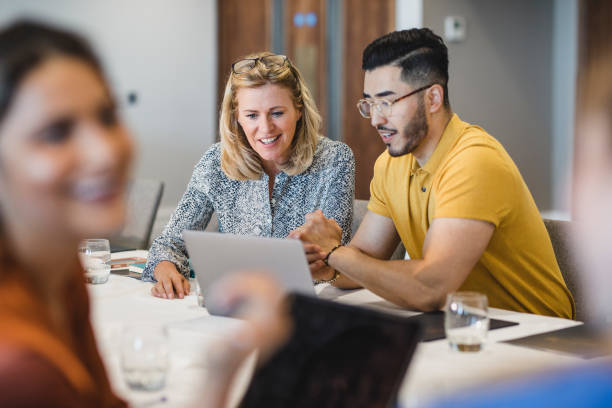 Hipster young man showing female colleague laptop Mature businesswoman smiling with employee, working together, collaboration, teamwork happy boss stock pictures, royalty-free photos & images