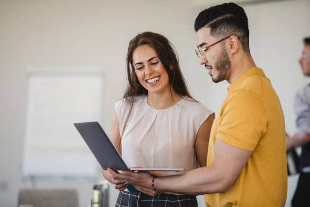 Hipster young man using laptop with cheerful female colleague stock photo