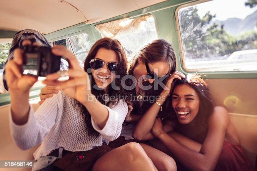 Three happy hipster young women taking selfie sitting in a vintage van during a summer road trip