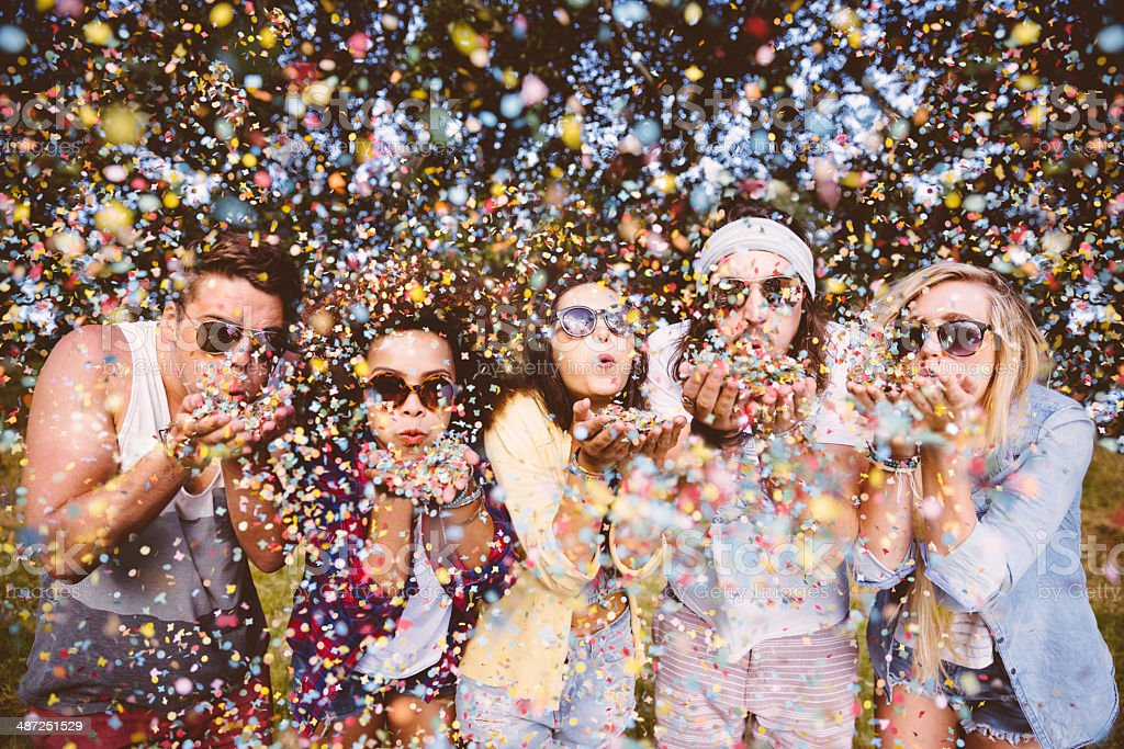 Hipsters blowing confetti stock photo