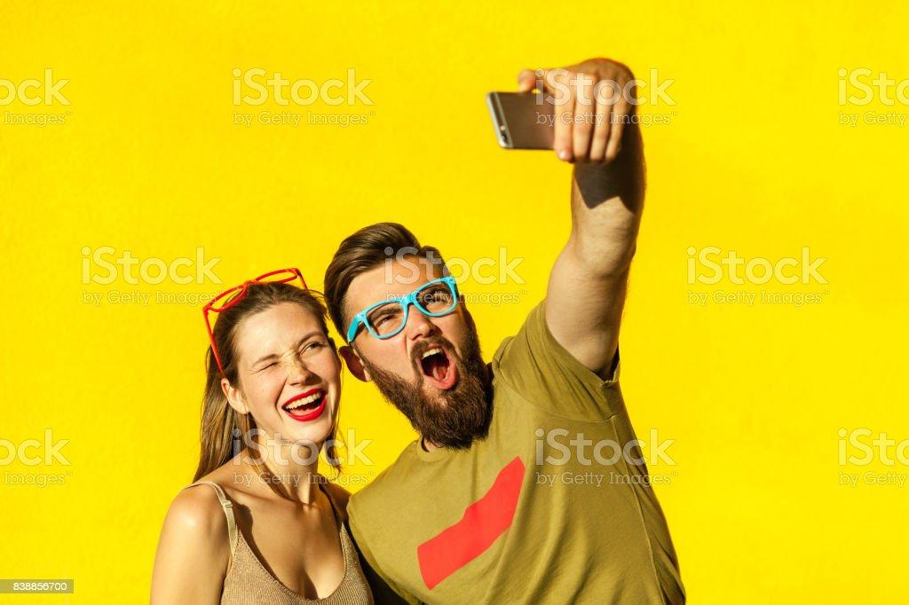 Hipsters pareja macking selfie sobre fondo amarillo - foto de stock