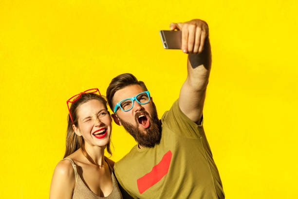 Hipsters couple macking selfie on yellow background stock photo
