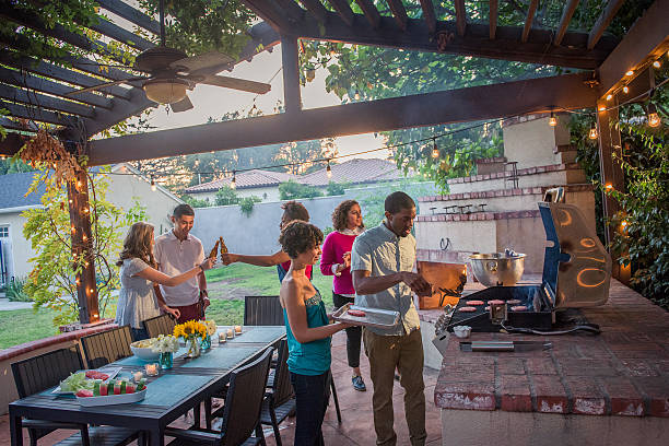 hipsters grilling at a summer backyard bbq - pergola stock-fotos und bilder