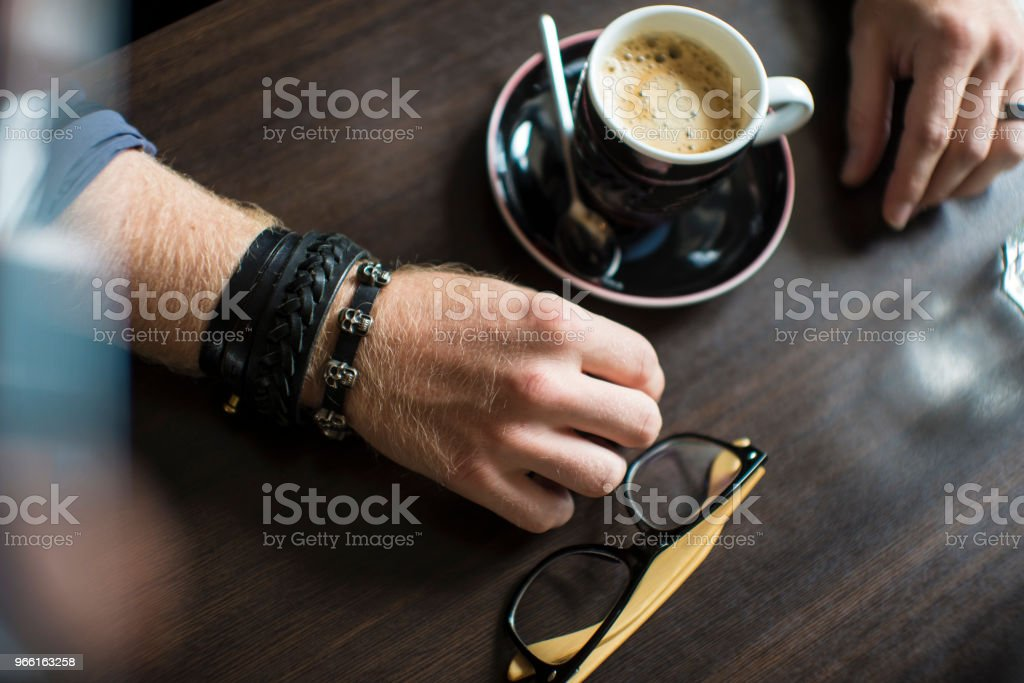 hipster's hands with a cup of coffee in the cafe at the table, close-up - Royalty-free Adult Stock Photo