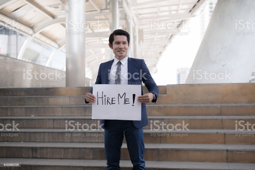 Hire me! Handsome businessman wear blue suit holding poster with hire me text message while standing outdoors and against building structure stock photo
