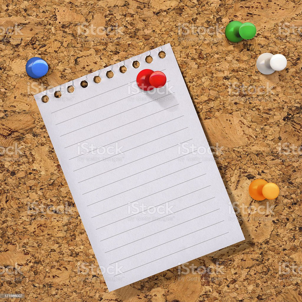 Hi-Res Lined Notebook Paper Pinned On A Cork Bulletin Board royalty-free stock photo