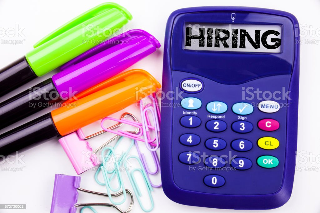 Hiring text in the office with surroundings such as marker, pen writing on calculator. Business concept for Recruitment and Job recruiting advertisement white background with copy space stock photo