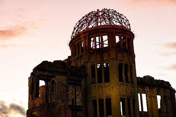 Hiroshima A-Bomb Dome Genbaku Domu Hiroshima A-Bomb Dome, Genbaku Domu, against evening red sky. A-Bomb Dome in Hiroshima,the first atomic bomb to be used in war detonated almost directly above the dome on August 6, 1945. hiroshima prefecture stock pictures, royalty-free photos & images